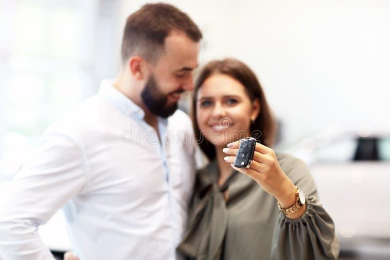 Volwassen paar die nieuwe auto in toonzaal kiezen stock fotografie