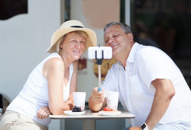 Volwassen paar die selfie met celtelefoon nemen stock afbeelding