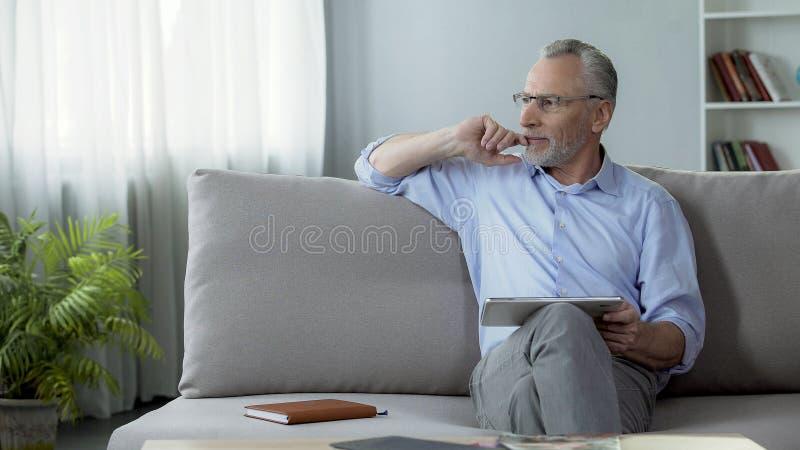 Volwassen persoonszitting op laag en het boeken van een hotelruimte voor vakantie op tablet stock afbeeldingen