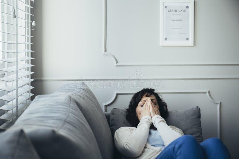 Volwassen psychotherapist is vermoeid met haar vreselijk werk stock afbeelding