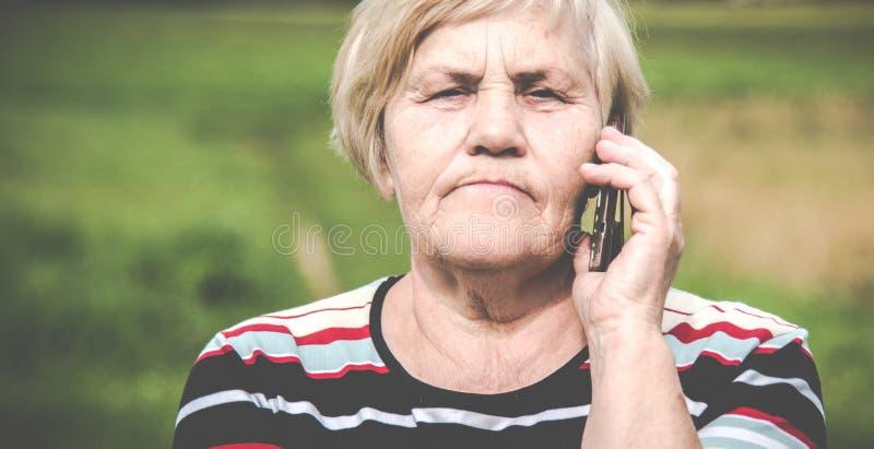 Volwassen rijpe Kaukasische vrouw die op een telefoon spreken stock foto's