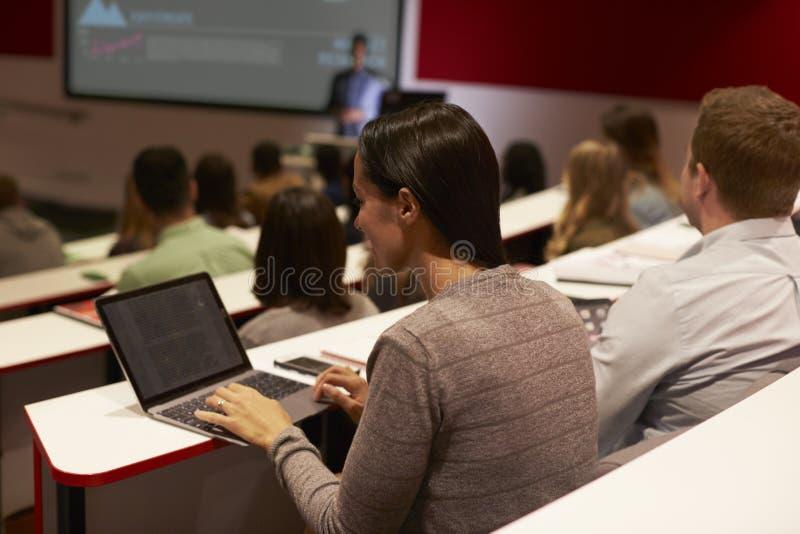 Volwassen student die laptop computer met behulp van bij een universitaire lezing stock foto's