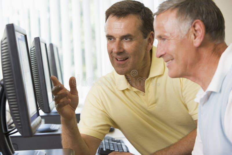 Volwassen studenten die aan computers werken stock afbeeldingen