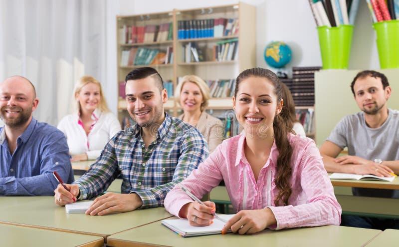 Volwassen studenten die in klaslokaal schrijven stock afbeeldingen