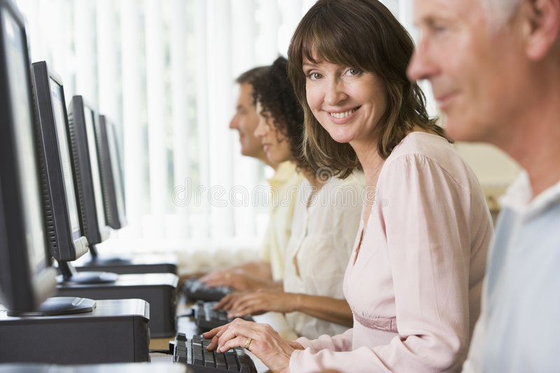 Volwassen studenten in een computerlaboratorium stock foto