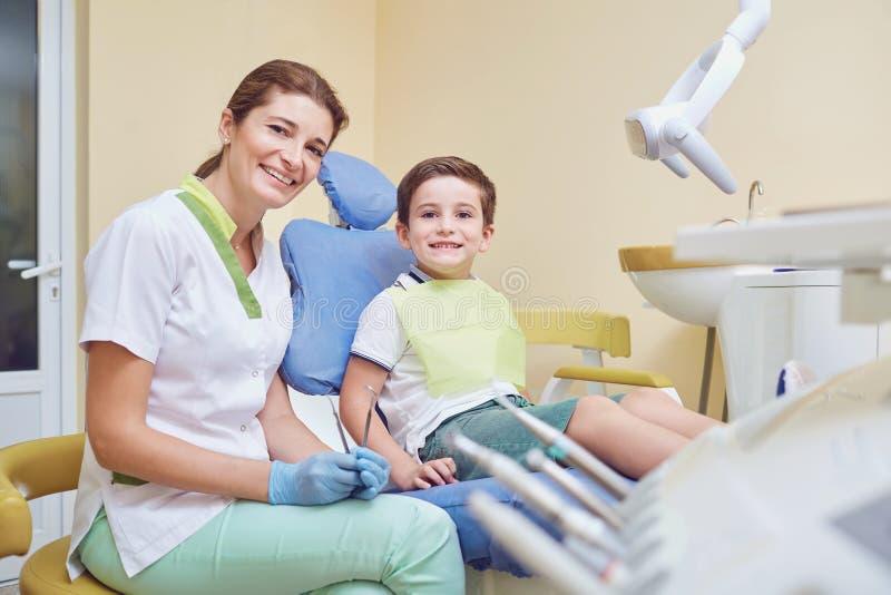 Volwassen tandarts met weinig patiënt in het ziekenhuisbureau stock afbeeldingen