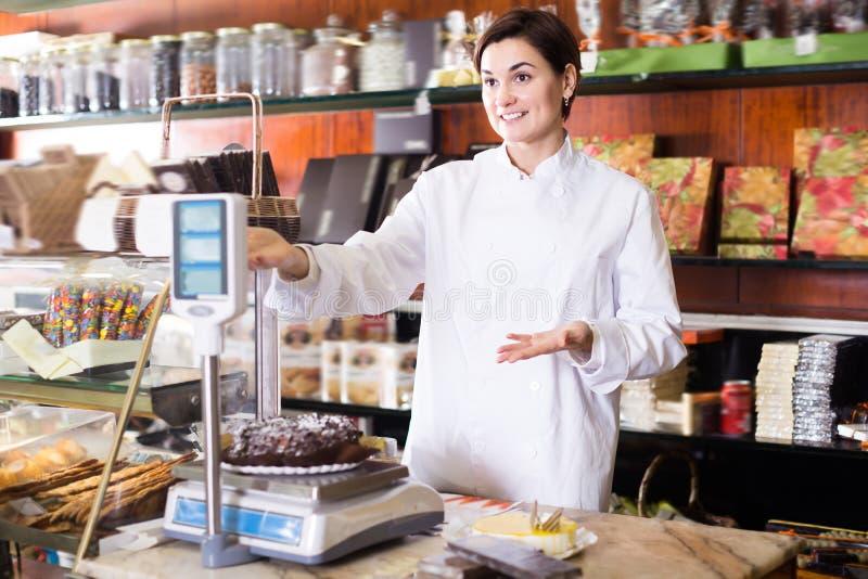 Volwassen verkoper die feestelijke chocoladecake wegen royalty-vrije stock foto's