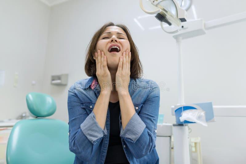 Volwassen vrouw die aan tandpijn lijden en tijdens bezoek aan professionele tandarts klagen royalty-vrije stock foto