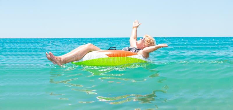 Volwassen vrouw die in een rubberring in het overzees drijven stock afbeeldingen