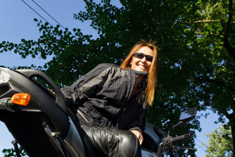 Volwassen Vrouw die Haar Motorfiets berijden stock fotografie