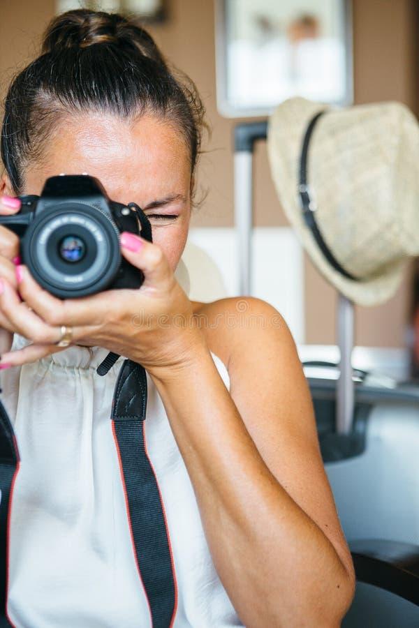 Volwassen vrouw die met camera streven stock foto