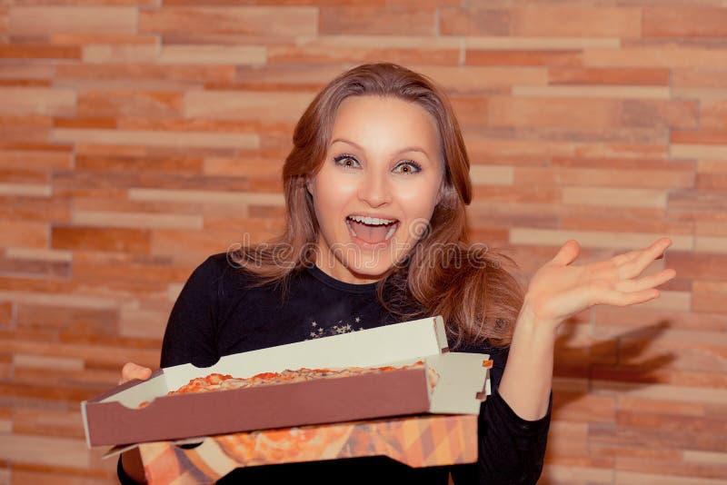 Volwassen vrouw die met gelukkige doos van pizza kijken royalty-vrije stock afbeelding
