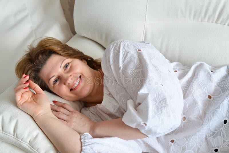 Volwassen vrouw die op de bank liggen royalty-vrije stock fotografie