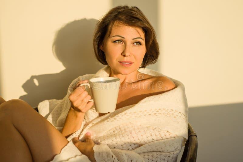 Volwassen vrouw die thuis op stoel voor venster het ontspannen het drinken koffie of thee zitten royalty-vrije stock foto