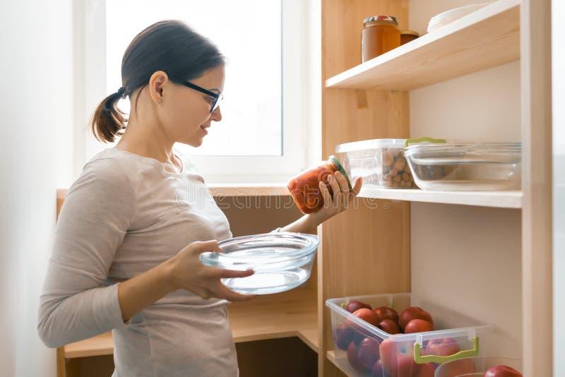 Volwassen vrouw het plukken voedsel van opslagkabinet in keuken, opslag met houten planken stock foto's