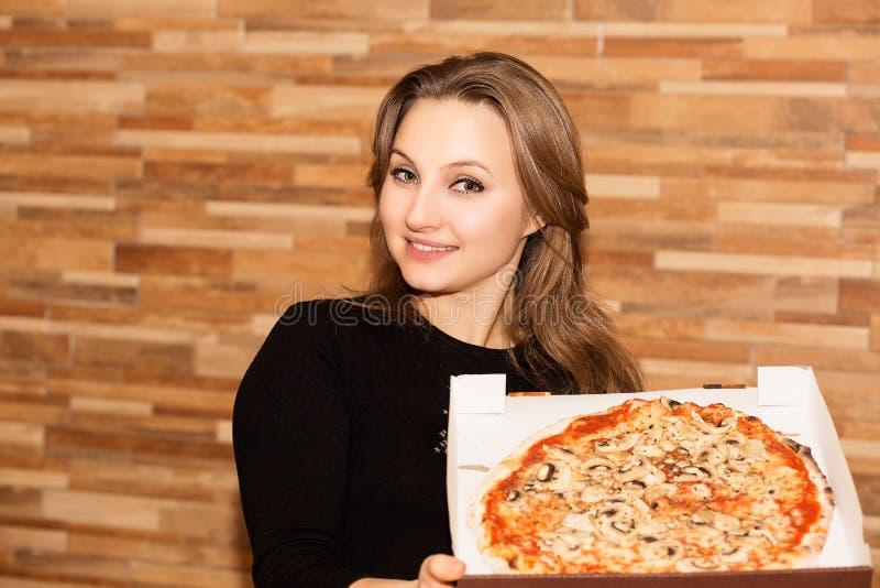 Volwassen vrouw met doos van pizza stock afbeeldingen