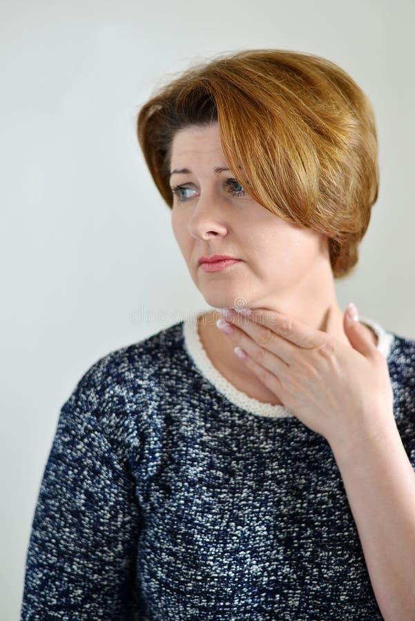 Volwassen vrouw met een keelpijn stock fotografie