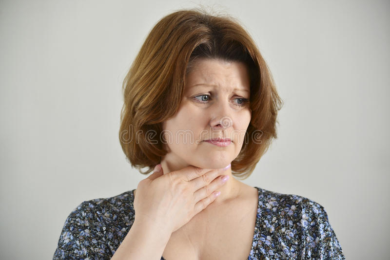 Volwassen vrouw met een keelpijn op lichte achtergrond stock afbeelding