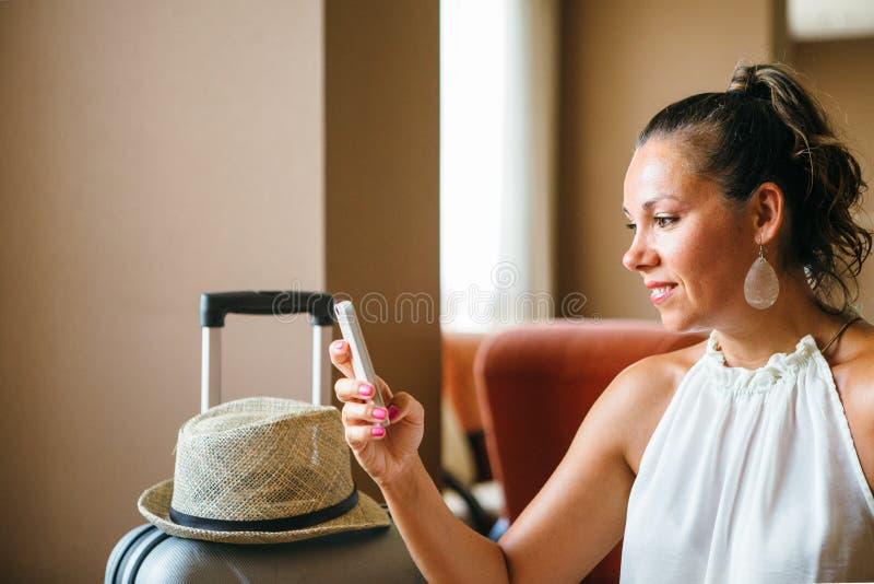 Volwassen vrouw met paardestaart die smartphone gebruiken stock afbeelding