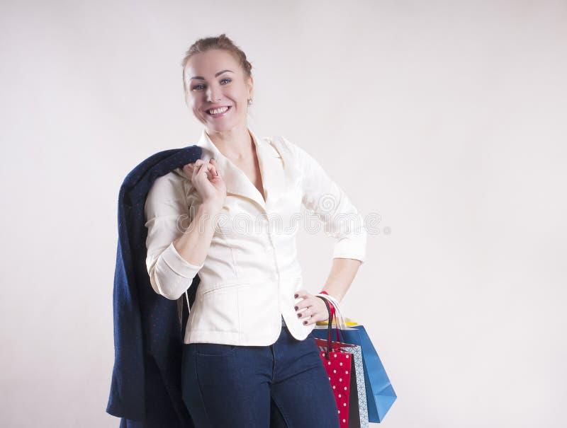 Volwassen vrouw met pakketten voor winkelende studiopersoon stock afbeeldingen