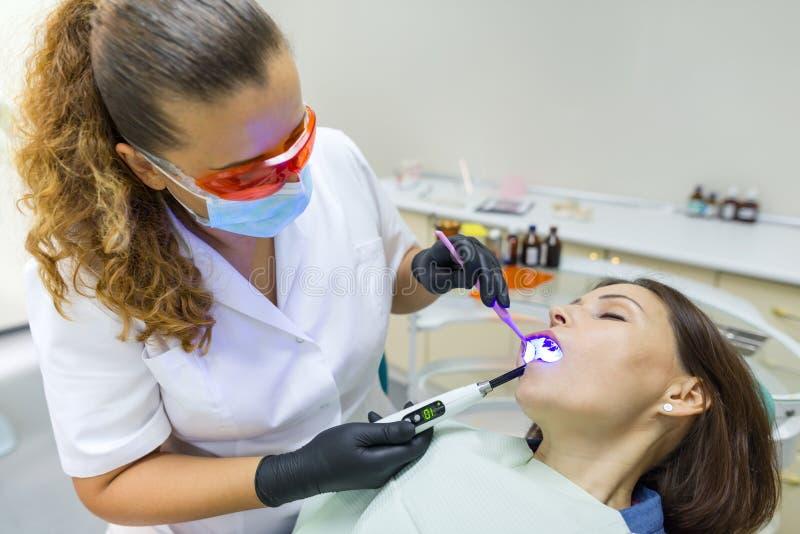 Volwassen vrouwelijke tandarts die geduldige vrouwentanden behandelen Geneeskunde, Tandheelkunde en Gezondheidszorgconcept royalty-vrije stock afbeeldingen