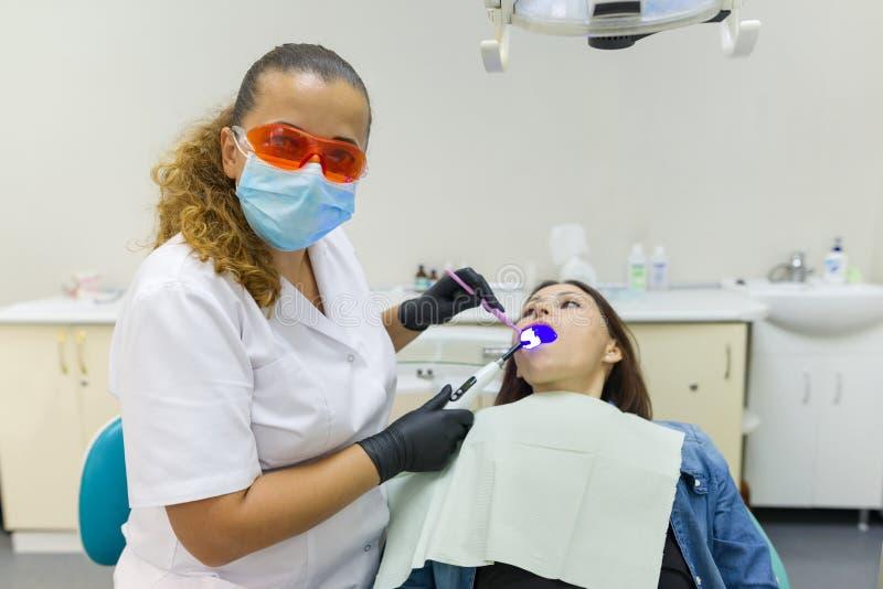 Volwassen vrouwelijke tandarts die geduldige vrouwentanden behandelen Geneeskunde, Tandheelkunde en Gezondheidszorgconcept royalty-vrije stock afbeelding