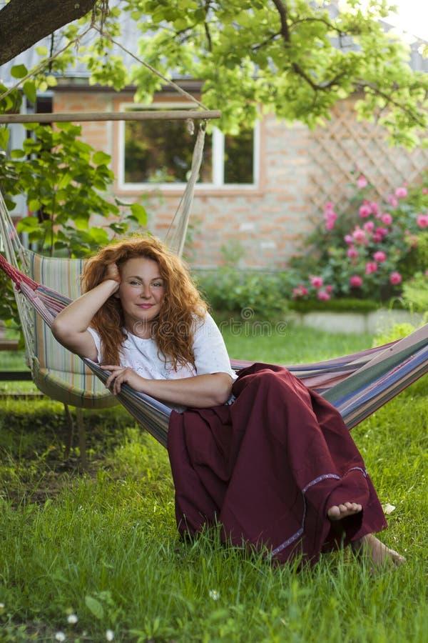 Volwassen vrouwen rustende hangmat in tuin van buitenhuis royalty-vrije stock foto