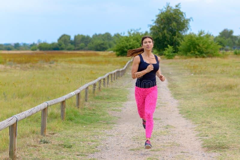 Volwassen vrouwenjogging naar camera langs weg royalty-vrije stock afbeeldingen