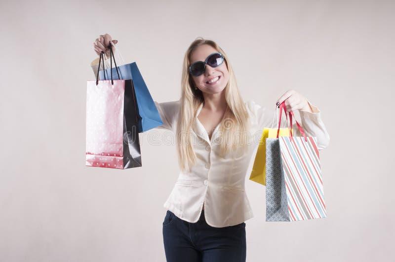 Volwassen vrouwenverrassing in een jasje met de aankopen van de pakkettenhuisvrouw in zonnebrilstudio royalty-vrije stock foto