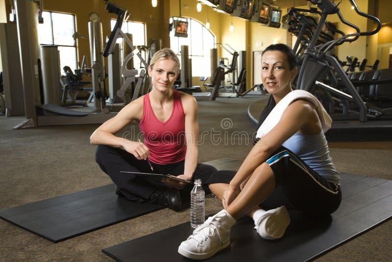 Volwassen wijfje met persoonlijke trainer bij gymnastiek. stock foto's