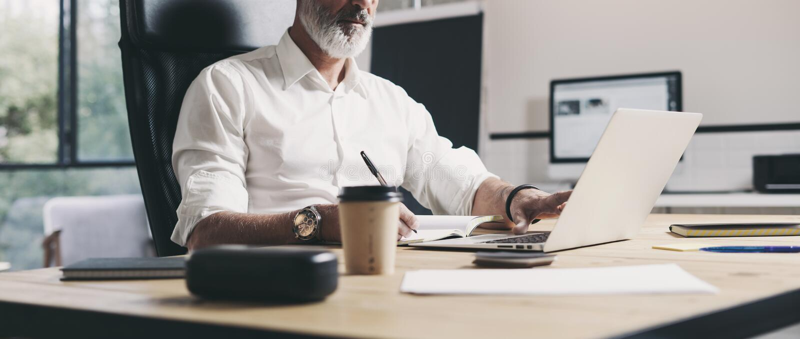Volwassen zakenman die op modern coworking kantoor werken Zekere mens die eigentijdse mobiele laptop met behulp van wijd royalty-vrije stock foto's