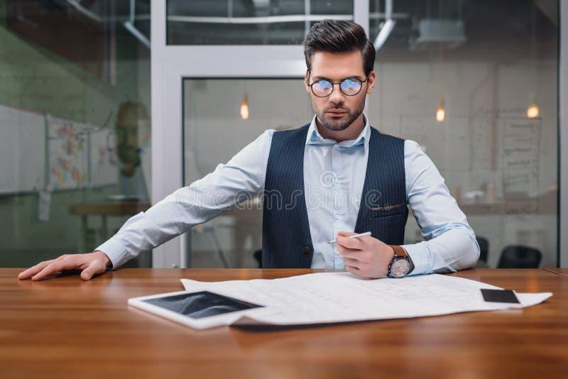 volwassen zakenman in oogglazen die met blauwdruk en gadgets werken stock foto