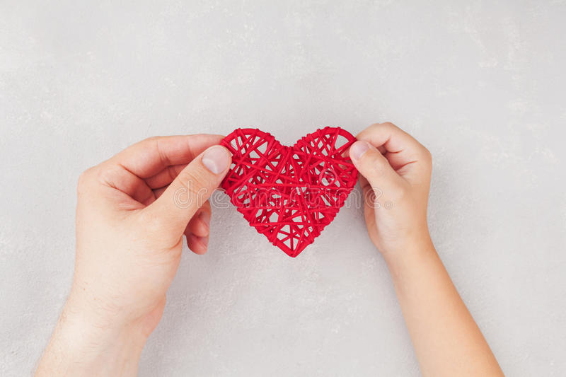 Volwassene en kind die rood hart in handen hierboven houden van Familieverhoudingen, gezondheidszorg, pediatrisch cardiologieconc royalty-vrije stock foto's