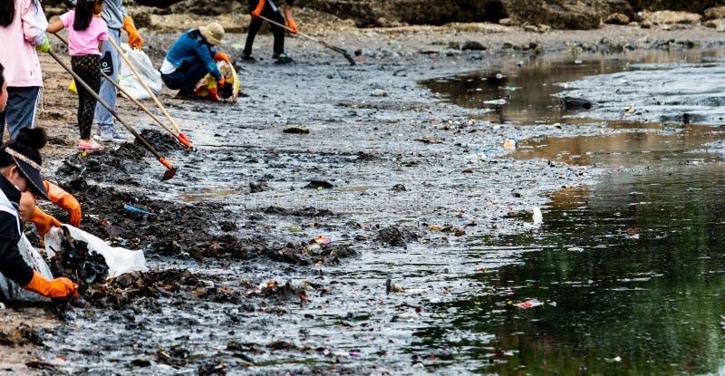 Volwassene en kinderenvrijwilligers die huisvuil op het overzeese strand verzamelen De verontreiniging van het strandmilieu Het o royalty-vrije stock afbeelding