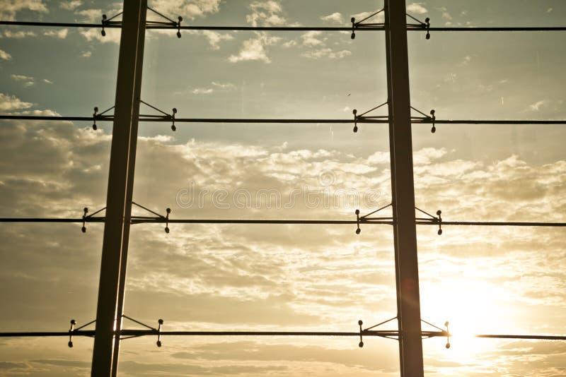 Vom Glas der Fensterwand, zum außerhalb des Sonnenuntergangs zu schauen lizenzfreies stockbild