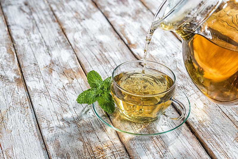 Vom Glaskrug wird ein Tee in eine Glasschale gegossen stockfotos