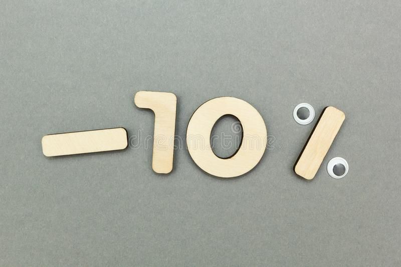 -10% von den hölzernen Zahlen auf einem grauen Papierhintergrund lizenzfreies stockbild