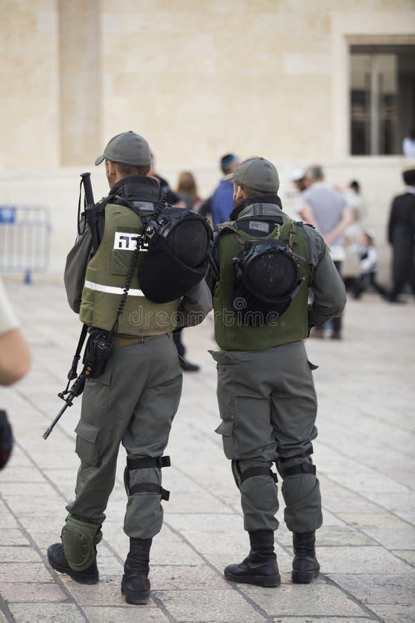 Von den hinteren zwei Männern in der Militäruniform und mit den Armen im b lizenzfreie stockbilder