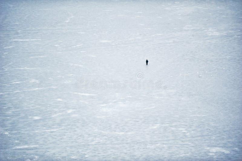 Von der Luftdraufsicht über einen gefrorenen See Einsamer Mann, der durch geht lizenzfreie stockfotografie