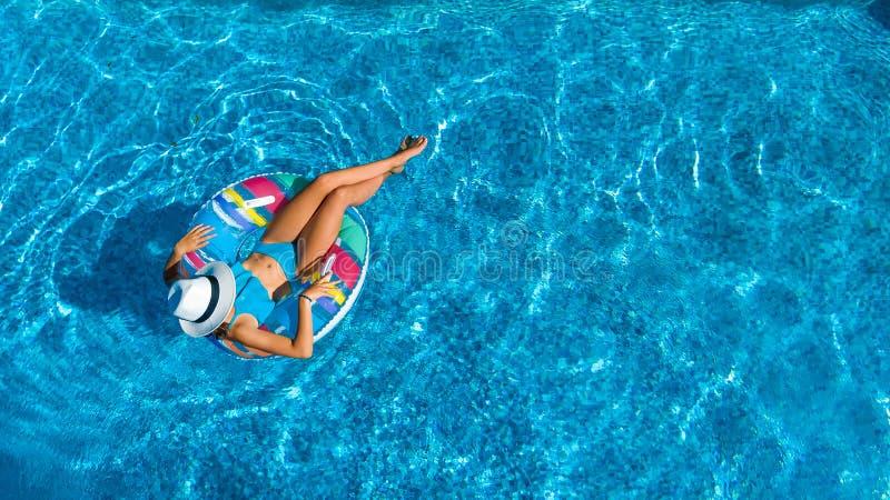 Von der Luftdraufsicht des schönen Mädchens im Swimmingpool von oben, entspannen sich Schwimmen auf aufblasbarem Ringdonut im Was stockfotografie