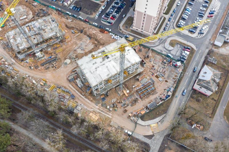 Von der Luftdraufsicht des Stadtbaubereichs mit unfertigen Gebäuden und Industriemaschinen stockbilder