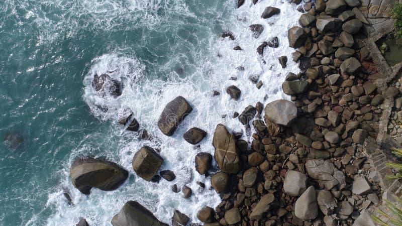 Von der Luftdraufsicht von den Meereswellen Felsen auf dem Strand in Phuket schlagend lizenzfreie stockfotos