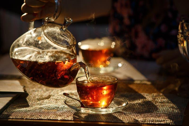 Von der transparenten Glasteekanne gießen Sie schwarzen Tee im Glasbecher, glüht lizenzfreies stockfoto