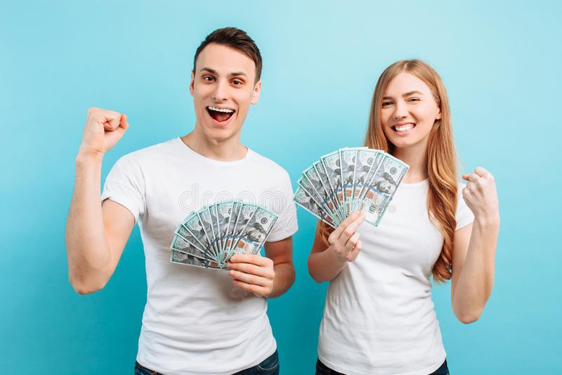 Von einem glücklichen jungen Paar macht ein Mann und eine Frau, die Geld halten, eine Siegergeste, gegen einen blauen Hintergrund lizenzfreie stockfotografie