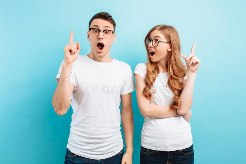 Von einem jungen Paar freuen sich ein Mann und eine Frau mit Gläsern, dass sie eine gute Idee in ihrem Kopf gegen einen blauen Hi lizenzfreie stockfotos