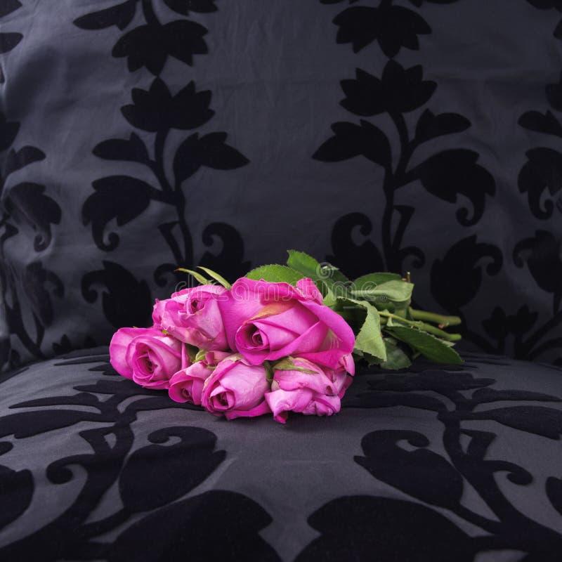 Von gestern rosafarbene Rosen verließen an einem schwarzen Samtsitz lizenzfreie stockbilder