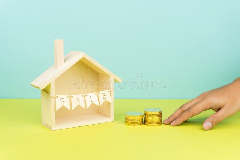 Von Hand eindrücken von zwei Stapeln der goldenen Münzen in Richtung zu einem Holzhaus stockfotografie