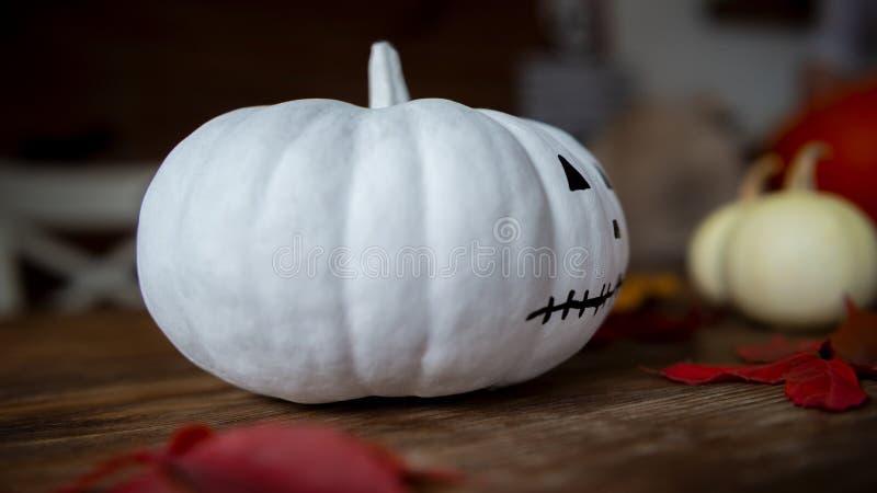 Von Hand verzierter weißer Kürbis mit gemaltem Gesicht und Herbstlaub auf Holztisch Dekoration zu Halloween lizenzfreies stockfoto