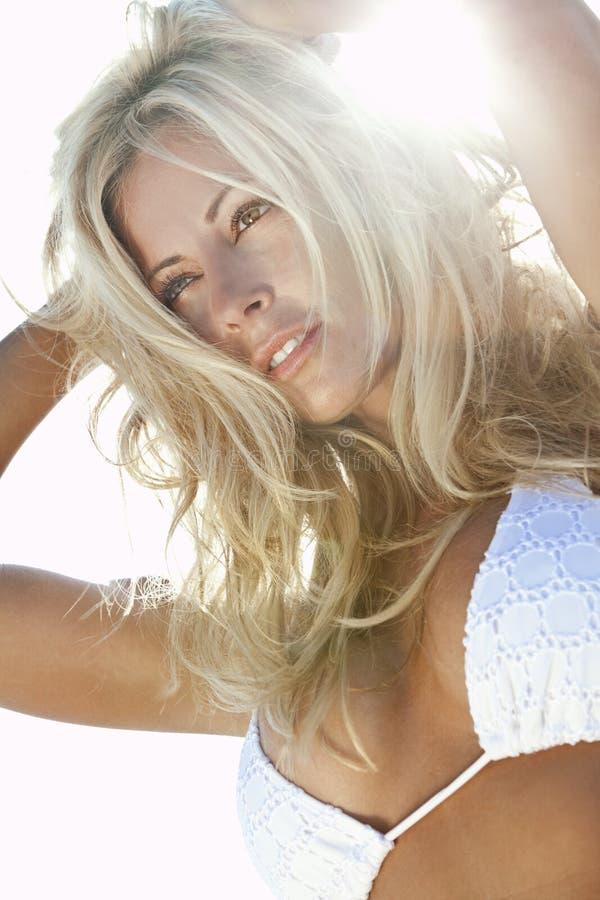 Von hinten beleuchtetes reizvolles blondes Mädchen im weißen Bikini lizenzfreies stockfoto
