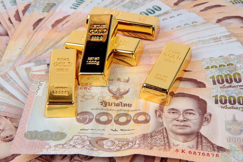 5 von 1 Kilogramm Goldbarren auf Baht 1000 Thailand-Banknoten nistete a stockbild